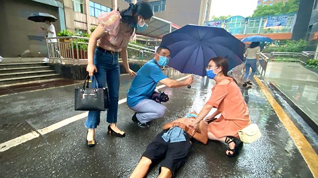 """雨中""""最美一跪"""" 90後女醫生救治昏迷男子"""